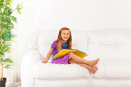 blond haired: Very happy and smart laughing little blond long haired girl sitting on the white couch with big yellow book Stock Photo