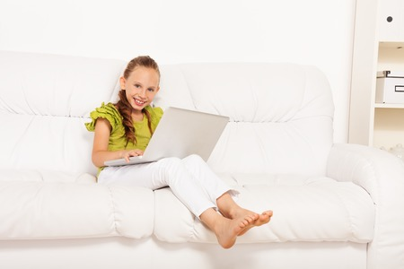 Cute little smiling happy girl sitting on the coach with laptop at home Stock Photo - 22511758