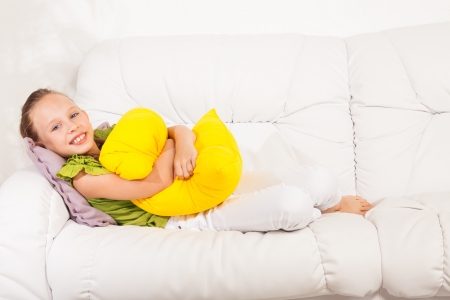 Happy smiling little girl 8 years old sitting with pillow on the white leather coach in living room at home Stock Photo - 22511767