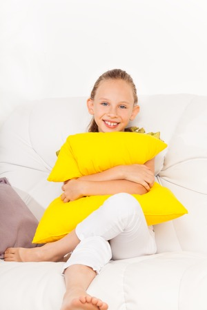 8 years: One happy little girl with big beautiful smile 8 years old sitting with pillow on the white leather coach in living room at home