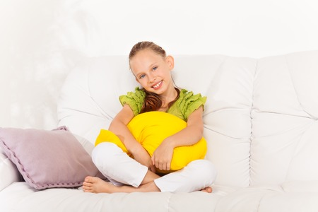 One happy little girl with big beautiful smile 8 years old sitting with pillow on the white leather sofa at home Stock Photo - 22511769