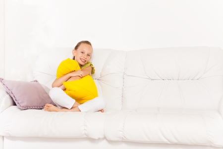 One happy smiling little girl 8 years old sitting with pillow on the white leather coach in living room at home Stock Photo - 22511770