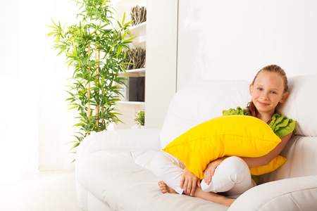One happy calm and relaxed girl 8 years old sitting with pillow on the white leather sofa in living room at home Stock Photo - 22511771