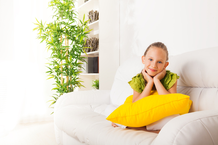 One shy little girl on the coach with pillow and with hands on the chin and nice smile Stock Photo - 22511772