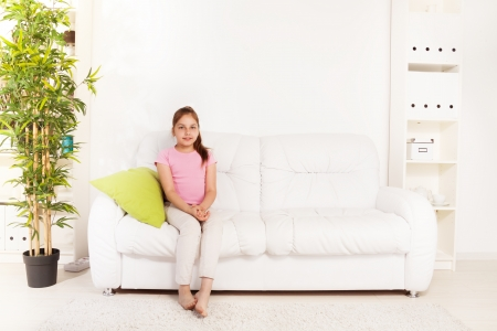 One happy calm girl 9 years old sitting with pillow on the white leather coach in home inter  Stock Photo - 22511774