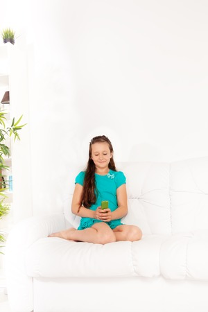 10 years old: Beautiful 10 years old girl texting on cell phone sitting on the the couch in living room