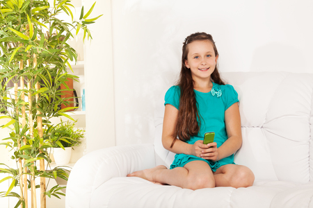 Little Caucasian girl with amazing big smile  SMS her friends sitting on the coach in living room photo
