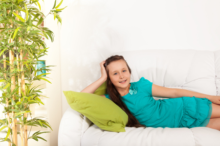 Happy nice  little girl 10 years old laying hugging pillow on the white coach in living room at home Stock Photo - 22511781