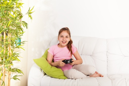 one little girl: Happy Caucasian girl playing video games holding game controller sitting on the coach in living room