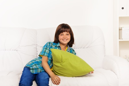 One happy calm and relaxed little boy 6 years old sitting with green pillow on the white leather coach in living room at home Stock Photo - 22416054
