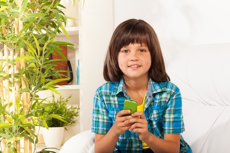 Closeup portrait of smilng little boy text using phone sitting on the coach Stock Photo