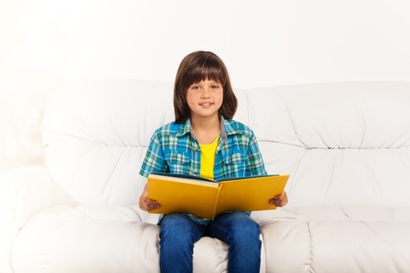 Smart calm 6 yeas old boy reading a big yellow book sitting in home interior on the sofa photo