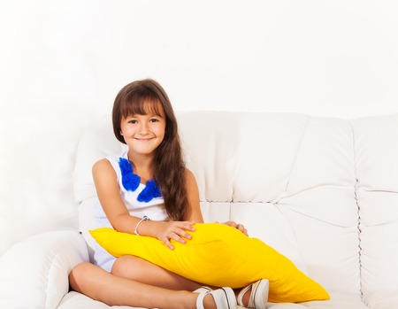six girls: One happy little girl sitting holding yellow pillow on the white leather sofa in living room at home Stock Photo