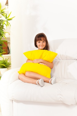 Happy joyful girl 6 years old sitting hugging pillow on the white coach in living room at home Stock Photo - 22416078
