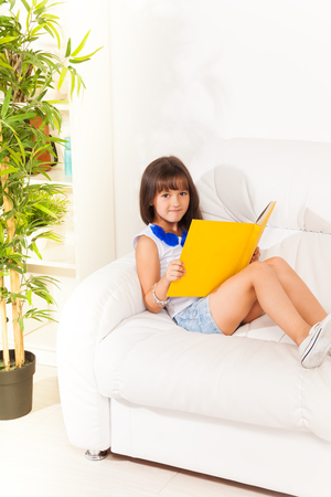 Nice brunet girl sitting and reading book on the sofa at home  photo