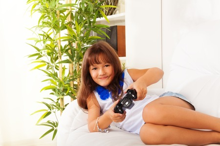 six girls: Schoolgirl with game controller laying on the sofa in living room at home