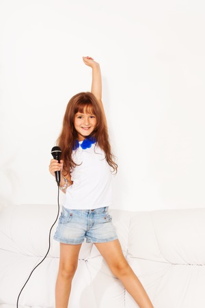 lifted hands: Close portrait of singing cute little rock star girl with microphone and lifted hands standing on the coach in home living room