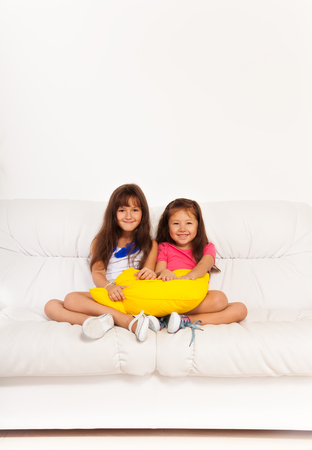 kids hugging: Two happy preschool , Asian and Caucasian calm and relaxed girls 6 years old sitting with pillow on the white leather coach in living room at home Stock Photo