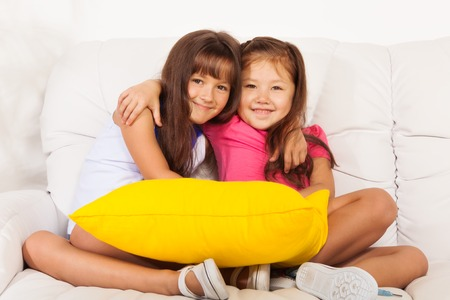 kids hugging: Two happy girls, Asian and Caucasian hugging together and sitting with pillow on the white leather coach in living room at home Stock Photo