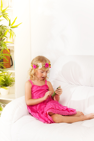 five years old: Little girl wearing wreath text her friends on social network sitting on the coach in living room Stock Photo