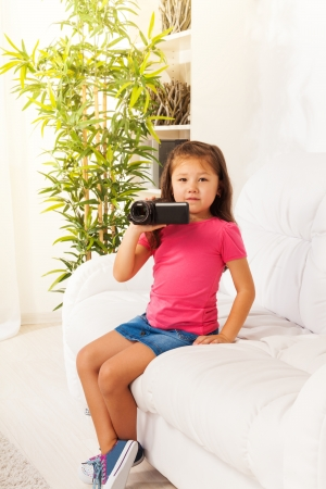 Cute little Asian girl shooting home movie with video camera sitting on the coach in living room photo