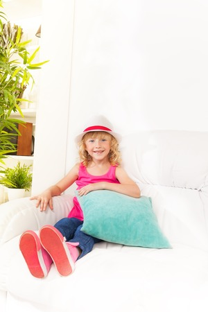 One happy calm and relaxed girl 5 years old sitting with pillow on the white leather coach in living room at home wearing white hat Stock Photo - 22416223