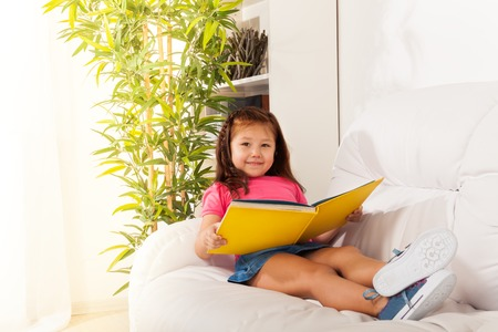 Little smart 5 years old girl laying on the sofa and reading book  photo