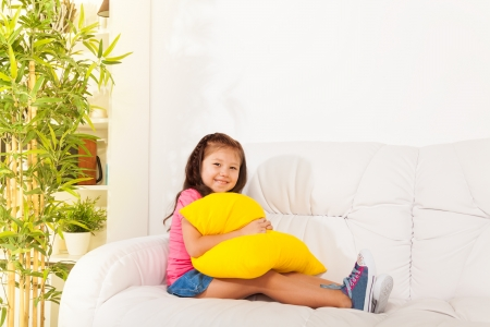 one little girl: One happy calm and relaxed Asian little girl 5 years old sitting with pillow on the white leather coach in living room at home Stock Photo
