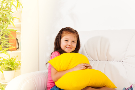 One happy calm and smiling girl 6 years old sitting with pillow on the white sofa in living room at home photo