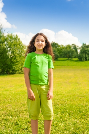 11: Beautiful happy smiling girl 11 years old in green shirt standing in the park Stock Photo