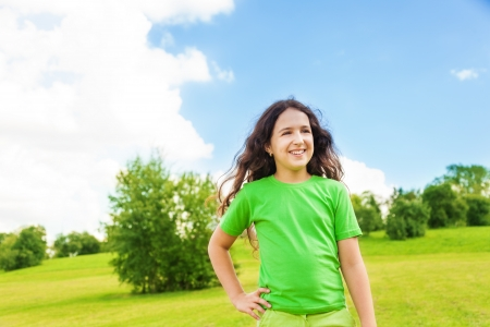 11: Beautiful happy lauging girl 11 years old in green shirt standing in the park