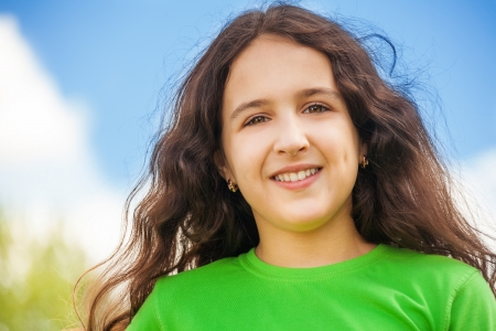11 years: Close-up portrait of beautiful happy smiling girl 11 years old in green shirt Stock Photo