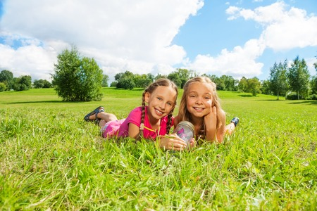 nine years old: Two happy little nine years old girls hold jar with butterfly laying in the grass and showing big smile on happy faces  Stock Photo