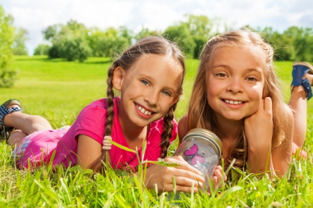 nine years old: Close-up of two happy little nine years old girls hold jar with butterfly laying in the grass and showing big smile on happy faces