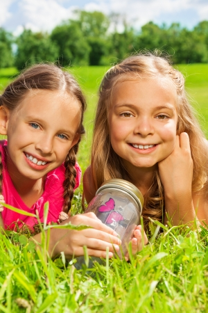 nine years old: Close-up portrait happy little nine years old girls friends hold jar with butterfly laying in the grass and showing big smile on happy faces Stock Photo
