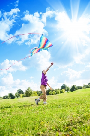 Happy eight years old nice boy playing in field with big color kite  photo