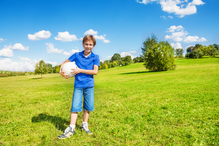 8 years: Nice smiling happy 8 years old boy stand with volleyball ball in the park field outside on sunny summer day
