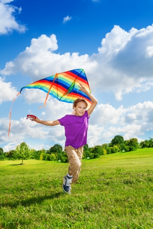 Happy eight years old nice boy running in the field with big color kite  photo