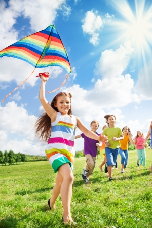 field stripped: Little smiling girl running with kite and her happy friends together in the park Stock Photo