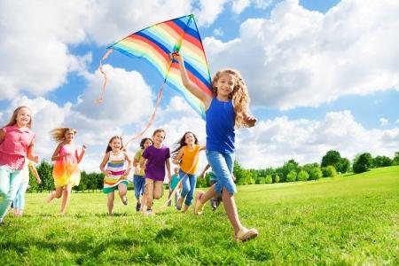papalote: Feliz ni�a sonriente con el pelo largo con otros chicos y chicas ni�os corriendo detr�s de ella Foto de archivo