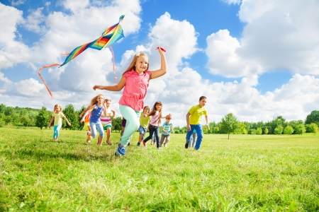 niño corriendo: Niña feliz que se ejecuta con la cometa y sus amigos en el campo verde de verano en un día soleado