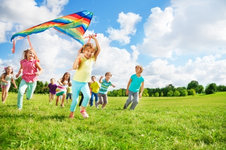 Cute little happy boys and girls running with kite together on sunny day having lots of fun