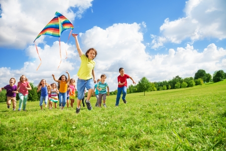 Boy running with kite with large group of friends, boys and girls running after