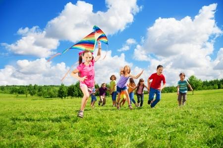 Gelukkig lachend meisje in roze met lange haren met andere kinderen jongens en meisjes die na haar Stockfoto