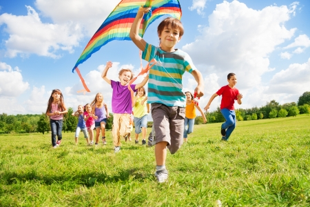field stripped: Many happy kids run together with kite on sunny summer day Stock Photo