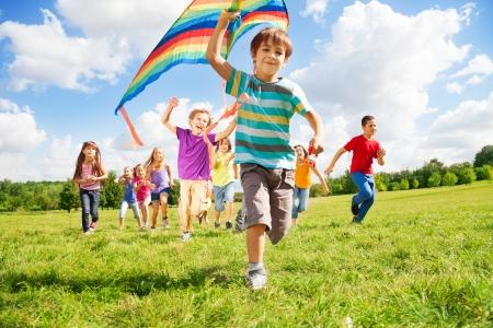 Vele gelukkige kinderen rennen samen met vlieger op zonnige zomerdag