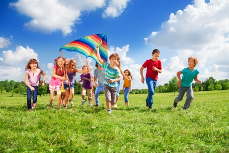 Large group of beautiful kids boys and girls running with kids in the park