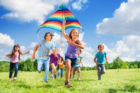 Vele gelukkige actieve kinderen jongens en meisjes lopen met vlieger in het park Stockfoto