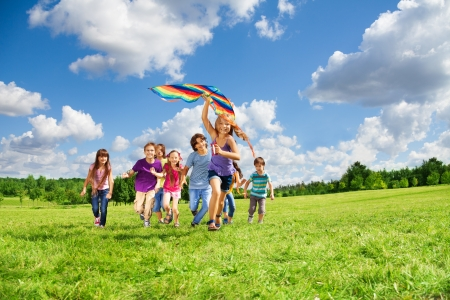 Cute happy active kids boys and girls run with kite in the park and having fun