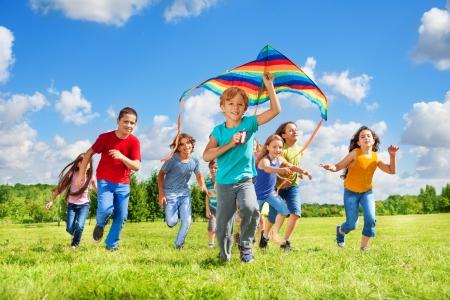 papalote: Feliz niño pequeño sonriendo con la cometa que se ejecuta en el parque con la cometa y el grupo de amigos en el parque el día soleado de verano Foto de archivo